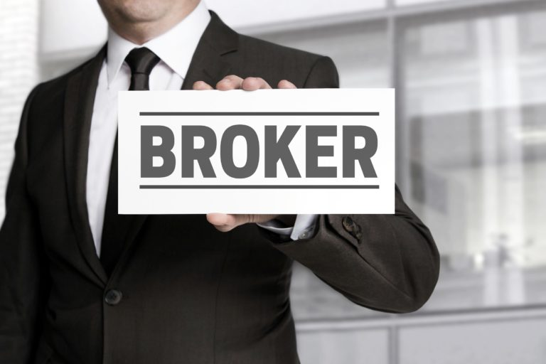 "A man holding up a sign saying ""Broker""."