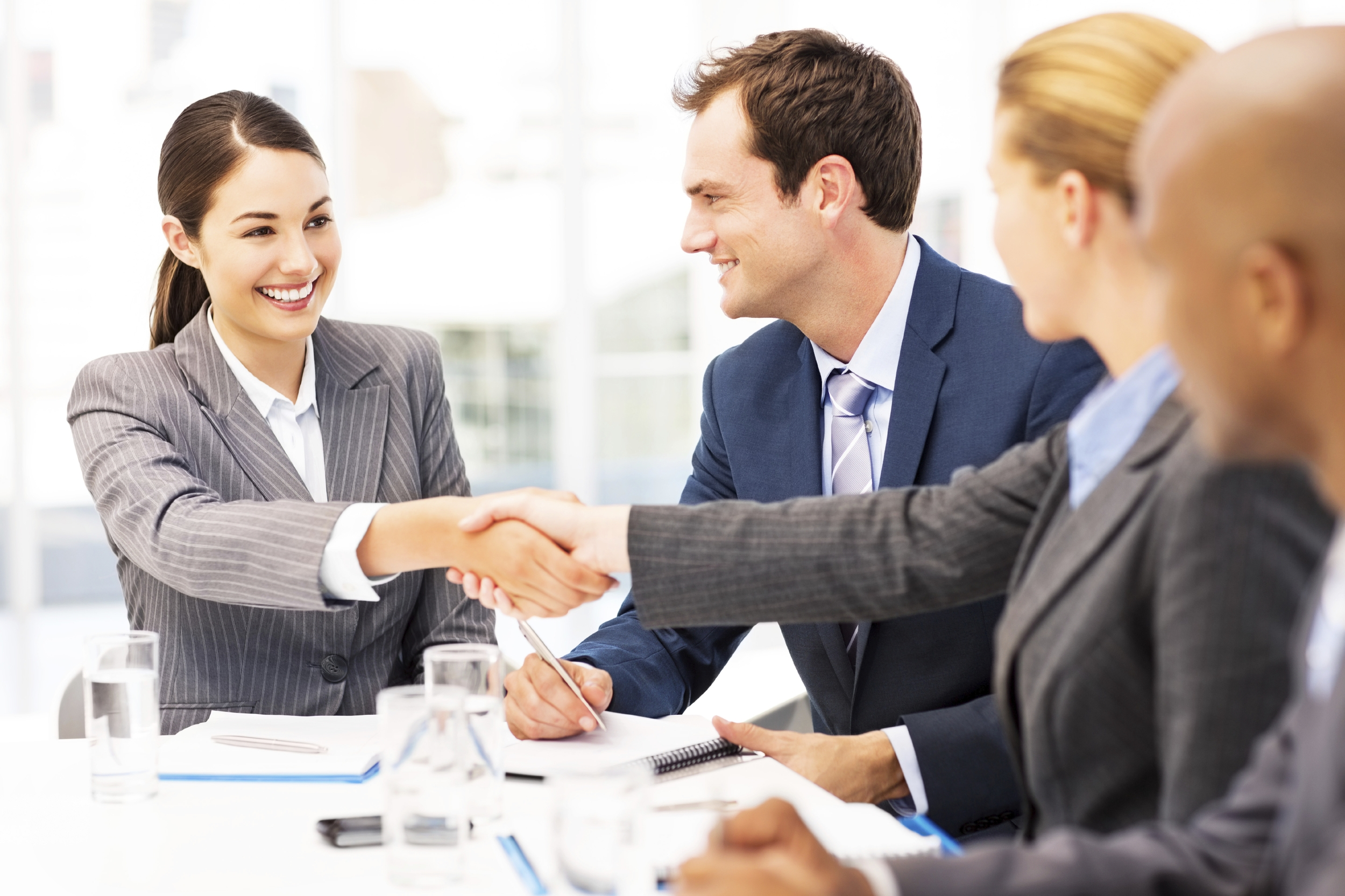 A positive business meeting with two women shaking hands.